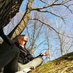 Belinda Steinle auf großem Baum sitzend, blauer Himmel
